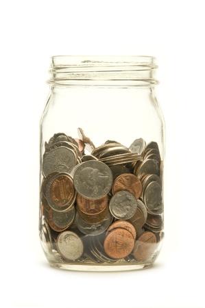 Amerikaanse munten in een glazen pot tegen een witte achtergrond