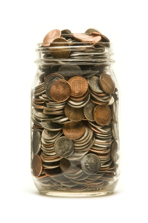 pennies: Glass jar almost overflowing with American coins against a white background Stock Photo