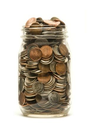 casi: Tarro de cristal casi llena de monedas de Am�rica sobre un fondo blanco