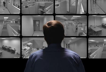 Bewaker uitvoeren van toezicht door te kijken naar verschillende security monitors Stockfoto