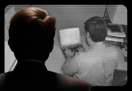 big brother spy: Man observing an employee work via a closed-circuit video monitor