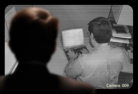 desconfianza: Hombre observar un trabajo de los empleados a trav?s de un monitor de video en circuito cerrado