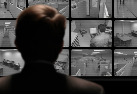 big brother spy: Man watching an employee work via a closed-circuit video monitor Stock Photo