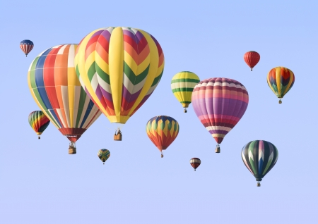 air: A group of colorful hot-air balloons floating across the sky