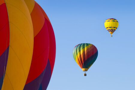 Multi-colored hot-air balloons with another in foreground Imagens