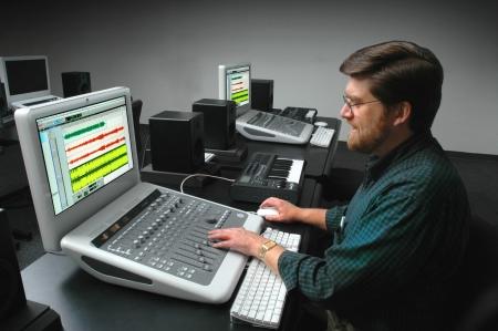 Man aan het werk op een digitaal geluid mengpaneel
