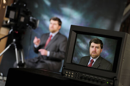 Monitor in production studio showing newsman or pundit talking to television or video camera