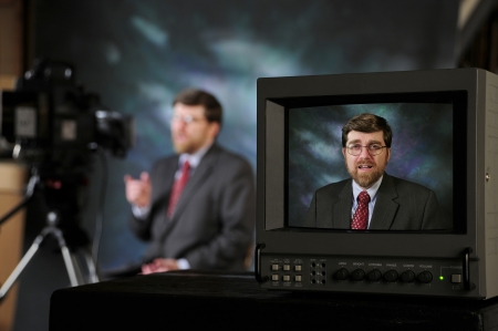 Monitor in production studio showing newsman or pundit talking to television or video camera Horizontal