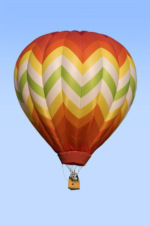 ballooning: Hot-air balloon floating against blue sky background