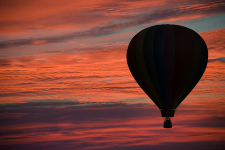 airborne vehicle: Hot-air balloon floating among pink and orange clouds at dawn