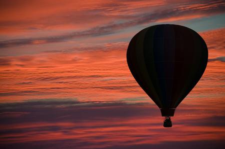ballooning: Hot-air balloon floating among pink and orange clouds at dawn