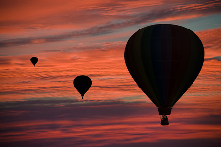 Hot-air balloons floating among pink and orange clouds at dawn