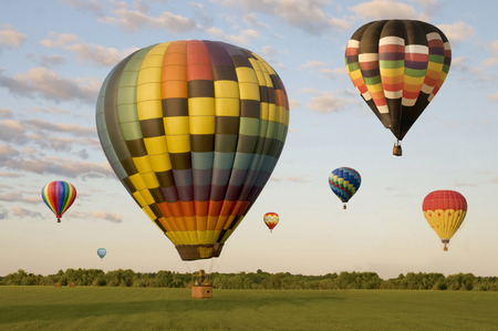 Various hot-air balloons landing in a field. One is on the ground. Others are floating.