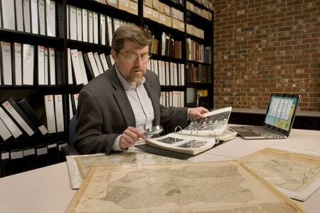 Researcher in archive, searching through maps and photographs. Model released. (All maps and photos shown in archive are public domain. Image on computer was created for this photograph.) Publikacyjne