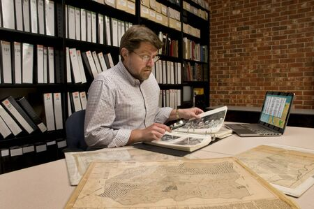 Researcher in archive, searching through maps and photographs. [Maps and photographs shown are public domain. Image on computer was created for this photograph. Model & Property Released.]