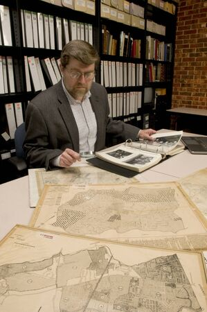 curator: Researcher in archive, searching through maps and photographs. [Maps and photographs on table are public domain. Image on computer creted for this photograph. Model and Property Released.]