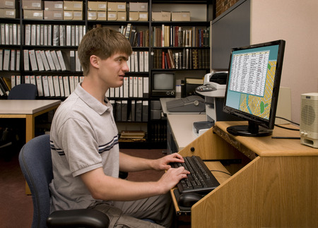 College student conducting computer research in a library archive. [Images on the computer screen were created for this photograph.]
