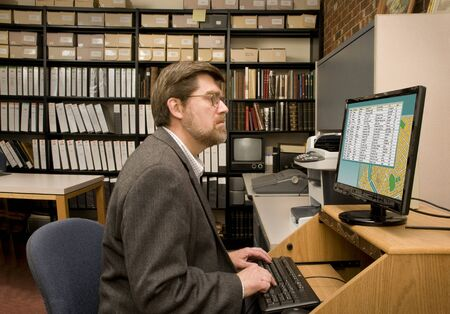 data entry: Researcher searching a computer database archives. [Images on the computer screen were created for this photograph.] Editorial