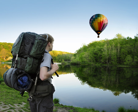 encounters: Backpacking hiker encounters a hot air balloon floating above a lake or pond Stock Photo