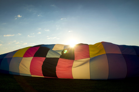 hotair: Sun peaking over the inflating envelope of a hot-air balloon
