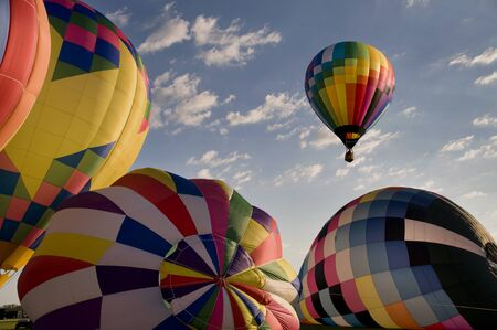 ballooning: One hot-air balloon ascending above other inflating balloons at a festival. (Readington Balloon Festival) Stock Photo