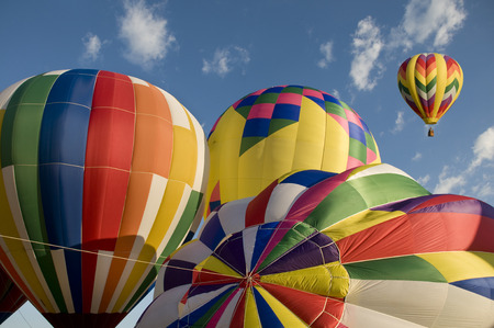 aloft: Colorful Hot-air balloons inflating with another balloon already aloft at the Readington Balloon Festival Stock Photo