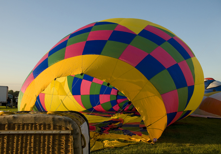 hotair: The colorful envelope of a hot-air balloon being inflated on the ground.