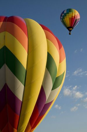 hot air balloons: Colorful hot air balloons launching against a blue sky Stock Photo