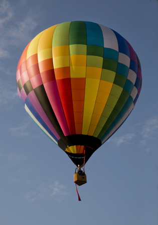 flying float: Colorful hot air balloon launching against a blue sky