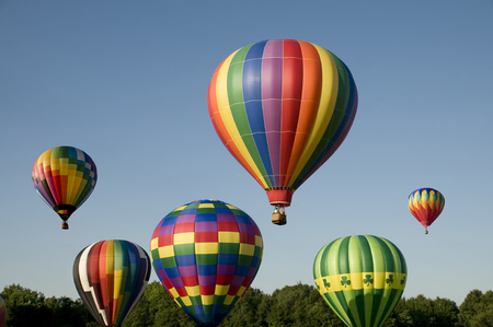 flight: Various hot-air balloons with colorful envelopes ascending or launching at a ballooning festival