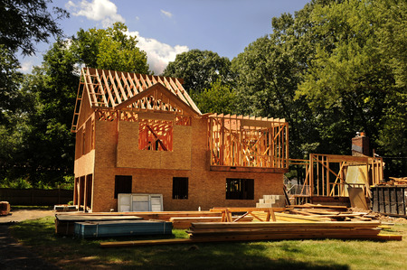 A residential home under construction mid framing and sheathing Stock Photo