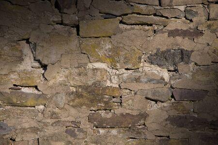 Cracked dilapidated masonry wall lit diagonally