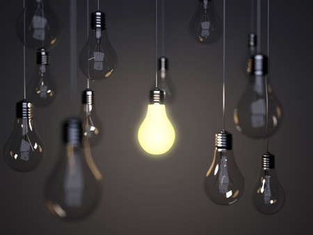 Light bulbs with one bright light bulb on a background a wall