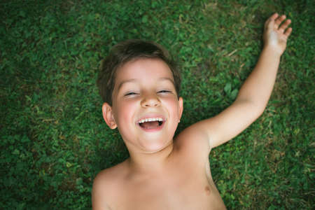 boys only: Portrait of a cute 5 year old boy lying on the grass with one arm raised behind his head Stock Photo
