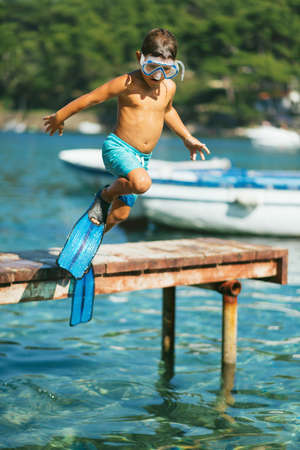 one boy only: Portrait of a beautiful sun tanned child jumping into the clear blue sea with a mask and flippers Stock Photo