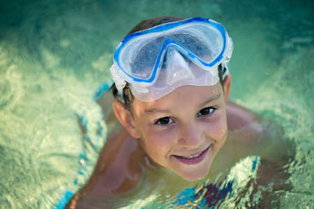 one boy only: Portrait of a happy, smiling boy in the crystal, clear blue sea with a mask on his forehead Stock Photo