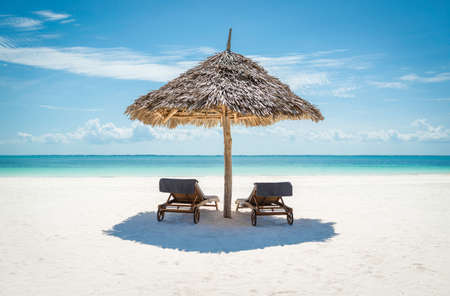 2 wooden sun loungers facing the tropical, turquoise blue Indian Ocean under a thatched umbrella on a white sandy Zanzibar beach