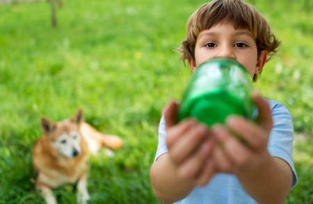 5 year old: Portrait of a cute 5 year old boy drinking water from a green bottle with a big dog watching him in the background
