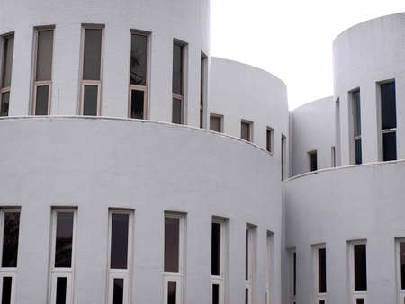 Part of circular white house with long windows