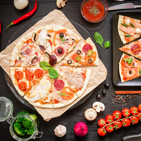 Pizza with ingredients, spices, oil and vegetables on black background. Flat lay, top view. Tasty italian food Standard-Bild