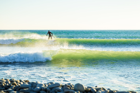 Surfing in the ocean. Clear green waves and surfer on wave