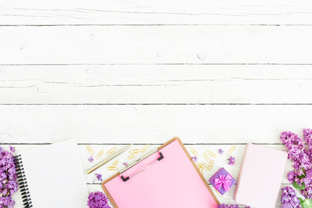 Minimalistic workspace with clipboard, notebook, pen, lilac, box and accessories on a wooden background. Flat lay, top view. Beauty blog concept.