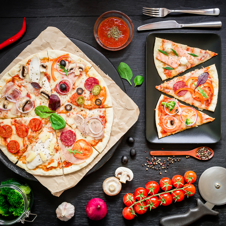 pizza cutter: Italian food. Pizza with ingredients, spices, oil and vegetables on black background. Flat lay, top view.