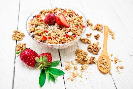 Oatmeal porridge with blueberries, nuts, strawberries and muesli on wood table. Top view. Diet breakfast.
