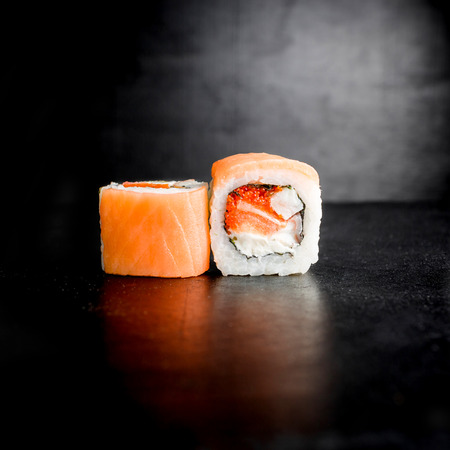 Sushi rolls with fish on black background. Japanese traditional food.