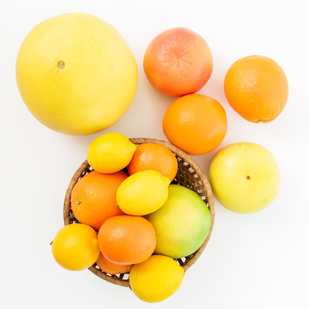 Citrus fruits in a plate on white background. Flat lay, top view. Fruit background.