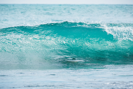 Blue barrel wave in tropical ocean. Wave crashing and sun light. Clear water. Stock Photo