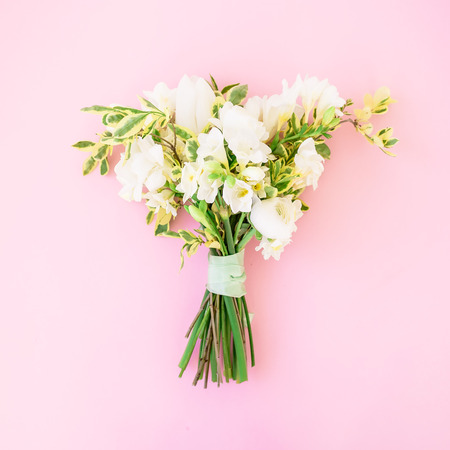 snapdragon: Wedding bouquet made of white flowers on pink background. Flat lay, top view. Wedding background. Stock Photo