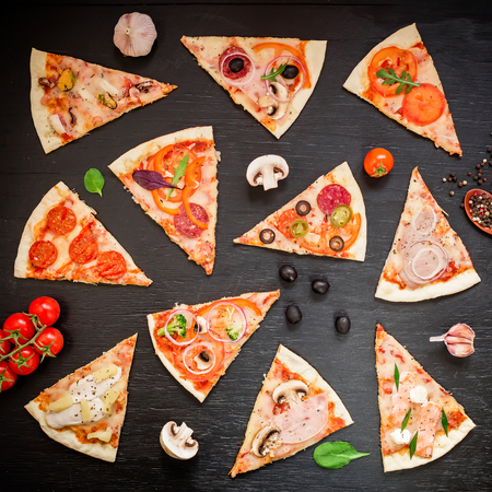 Pizza with ingredients and vegetables on black background. Flat lay, top view. Sliced ??pizza pattern