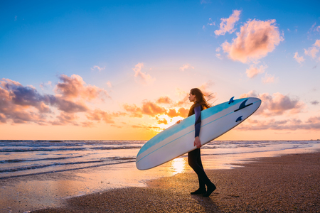 Young beautiful woman with long hair. Surf girl with surfboard on a beach at sunset or sunrise. Surfer and ocean